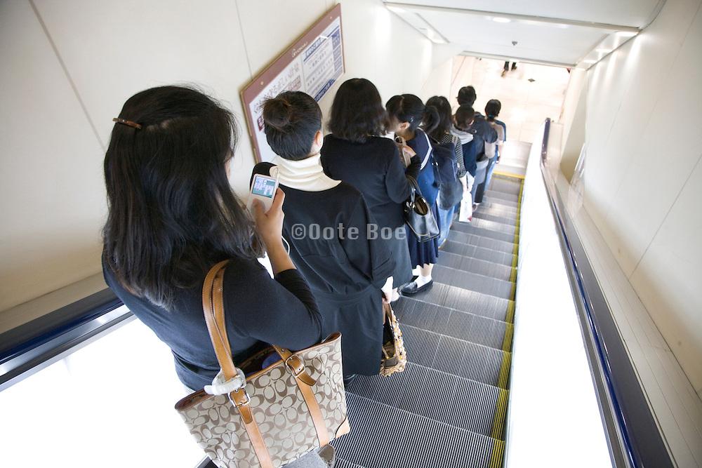 women going down an escalator inside a department store Tokyo Japan