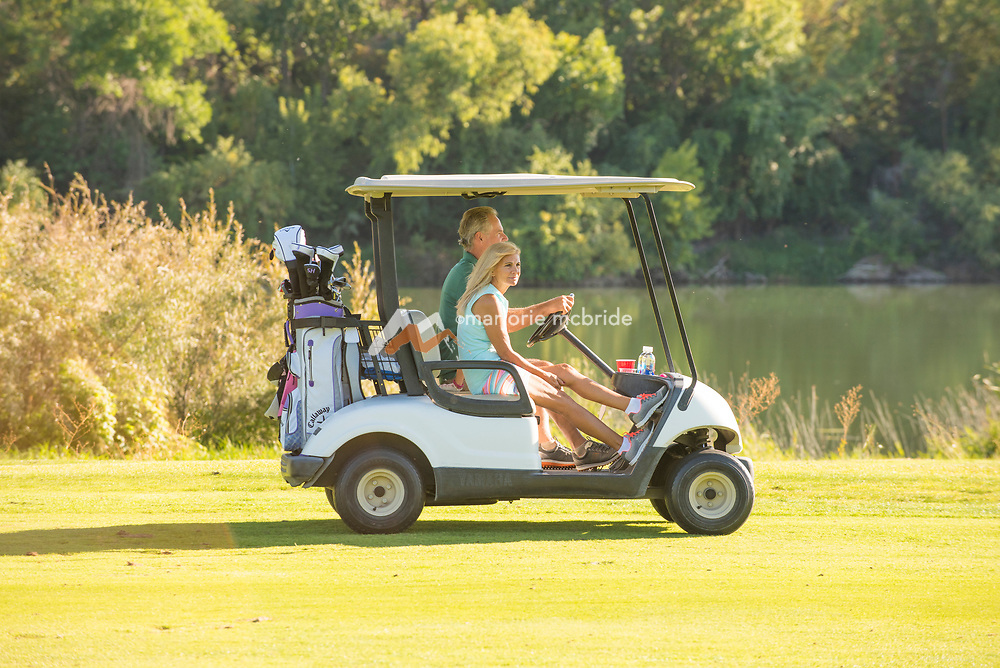 Senior couple golfing riding in cart along the Snake River at Clear Lakes Country Club in Buhl, Idaho. MR