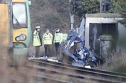 © Licensed to London News Pictures. 17/02/2018. Horsham, UK. Police stand near the remains of a car at a level crossing where two people have been killed near the village of Barns Green after a train hit a car. Photo credit: Peter Macdiarmid/LNP