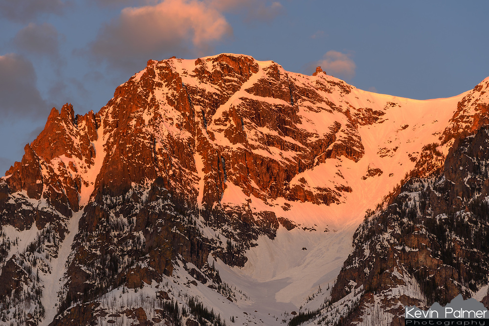 Morning sunlight illuminates an unnamed peak in Montana's Beartooth Mountains. This was the view I woke up to while camping in the East Rosebud Valley in Early May. In this mountain range are found dozens of glaciers, and the largest high elevation plateau in the US outside of Alaska. In the upper reaches of these steep slopes avalanche activity was high. A cornice, which is an overhang of snow caused by strong winds, can be seen on the upper right. Overnight the snow solidified as the temperatures cooled. But once the sunlight touched the snow and temperatures warmed, the snow became unstable and gave way. In my 10 mile hike through the wilderness I witnessed about 20 avalanches, most of them small. Sometimes I would hear them before I saw them, with the noise sounding like distant thunder. See below for a picture of one.