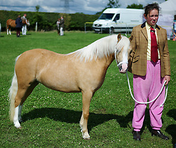 © Licensed to London News Pictures.29/07/15<br /> Borrowby, UK. <br /> <br /> A girl walks her horse around the paddock before her event at the Borrowby Country Show and Gymkhana in North Yorkshire.<br /> <br /> Photo credit : Ian Forsyth/LNP