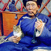 75-year old Gonchigsuren, a nomad,  relaxes with his cat in his ger (yurt), Darhad Valley, Mongolia.
