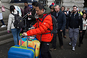 A tourist wheels colourful suitcases negotiates the evening rush-hour alongside ordinary commuters at Waterloo Station, on 4th March 2019, in London England.