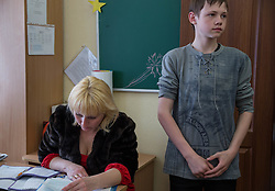 Sergey, 13, a resident of the Lugansk Orphanage No.1 has his homework checked by his  teacher Lena Alexandronova at the end of after school classes.