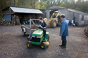 A teenage boy of 15 years of age learns the art of reversing a a small trailer on a family farmstead in north Somerset. While steering the small garden mower, he looks behind him to guage the way the front wheels turn against the rear - gaining experience of how opposite locks on their turning circles change the path of two interlinked vehicles. Giving instructions is an older man, the boy's granddad whose experience is passed on after a lifetime of handling the larger tractor in the background near his garage and wood shed.