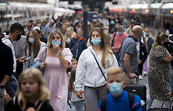 © Licensed to London News Pictures. 31/07/2021. London, UK. Members of the public wearing face masks disembark a train at Kings Cross Station in central London. The UK's COVID-19 cases continue to fall following the removal of restrictions on July 19th. Photo credit: Ben Cawthra/LNP