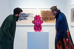 """© Licensed to London News Pictures. 12/10/2021. LONDON, UK.  Visitors view """"Dom Pèrignon Balloon Venus"""", 2013, by Jeff Koon, in front of """"Untitled"""", 1971, lithographs by Cy Twombly. Preview of """"Jeff Koons & Cy Twombly: Primal Gestures"""", an exhibition which brings together a highly unusual pairing of two giants of post-war art Jeff Koons and Cy Twombly.  The exhibition runs 12 October to 4 December 2021 at Bastian Gallery in Mayfair..  Photo credit: Stephen Chung/LNP"""