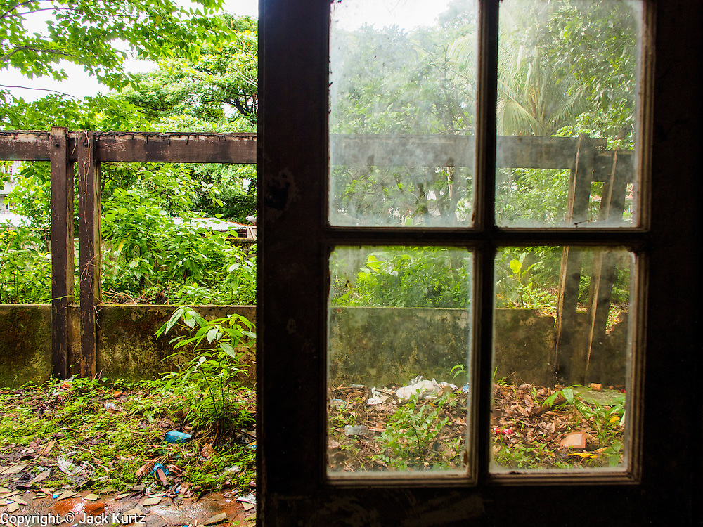 07 JUNE 2014 - YANGON, MYANMAR: A door out to the grounds of the Pegu Club. The Pegu Club in Yangon was the Officers' Club for the British Army when Myanmar was the British colony of Burma. The club, principally made of teak, is now abandoned and in decay. Squaters have moved into the parts of the complex still standing. Yangon has the highest concentration of colonial style buildings still standing in Asia. Efforts are being made to preserve the buildings but many are in poor condition and not salvageable.    PHOTO BY JACK KURTZ