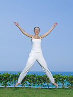 woman exercising jumping feeling happy by the seaside
