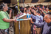 "12 JULY 2012 - FT DEFIANCE, AZ:      FLORENCE BARKER, from the Manuelito Church of God, leads the alter call at the 23rd annual Navajo Nation Camp Meeting in Ft. Defiance, north of Window Rock, AZ, on the Navajo reservation. Preachers from across the Navajo Nation, and the western US, come to Navajo Nation Camp Meeting to preach an evangelical form of Christianity. Evangelical Christians make up a growing part of the reservation - there are now more than a hundred camp meetings and tent revivals on the reservation every year. The camp meeting in Ft. Defiance draws nearly 200 people each night of its six day run. Many of the attendees convert to evangelical Christianity from traditional Navajo beliefs, Catholicism or Mormonism. ""Camp meetings"" are a form of Protestant Christian religious services originating in Britain and once common in rural parts of the United States. People would travel a great distance to a particular site to camp out, listen to itinerant preachers, and pray. This suited the rural life, before cars and highways were common, because rural areas often lacked traditional churches.PHOTO BY JACK KURTZ"