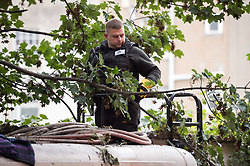 © Licensed to London News Pictures. 24/09/2019. Bristol, UK. Bailiffs from EAS Enforcement with the landlord and agents and police present, and being filmed by Channel 5 for television, attempt an eviction at 26 Picton Lane, Montpelier. A resident (in flat cap) can be seen on the roof of a van and building as bailiffs use a scissor lift to try and access the roof, after supporters of the resident try and block the lift from being brought to the site. Photo credit: Simon Chapman/LNP.