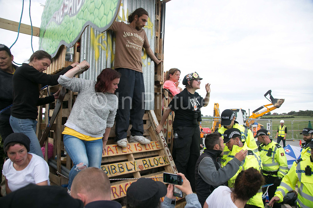 12 local activists locked themselves in specially made arm tubes to block the entrance to Quadrillas drill site in New Preston Road, July 03 2017, Lancashire, United Kingdom. Police forcing protestors away fro the gates. Activists up the make-shift tower prevent police form clearing that. The 13 activists included 3 councillors; Julie Brickles, Miranda Cox and Gina Dowding and Nick Danby, Martin Porter, Jeanette Porter,  Michelle Martin, Louise Robinson,<br /> Alana McCullough, Nick Sheldrick, Cath Robinson, Barbara Cookson, Dan Huxley-Blyth. The blockade is a repsonse to the emmidiate drilling for shale gas, fracking, by the fracking company Quadrilla. Lancashire voted against permitting fracking but was over ruled by the conservative central Government. All the activists have been active in the struggle against fracking for years but this is their first direct action of peacefull protesting. Fracking is a highly contested way of extracting gas, it is risky to extract and damaging to the environment and is banned in parts of Europe . Lancashire has in the past experienced earth quakes blamed on fracking.