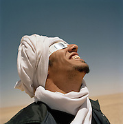 Man watching the Eclipse through protective glasses, Libya