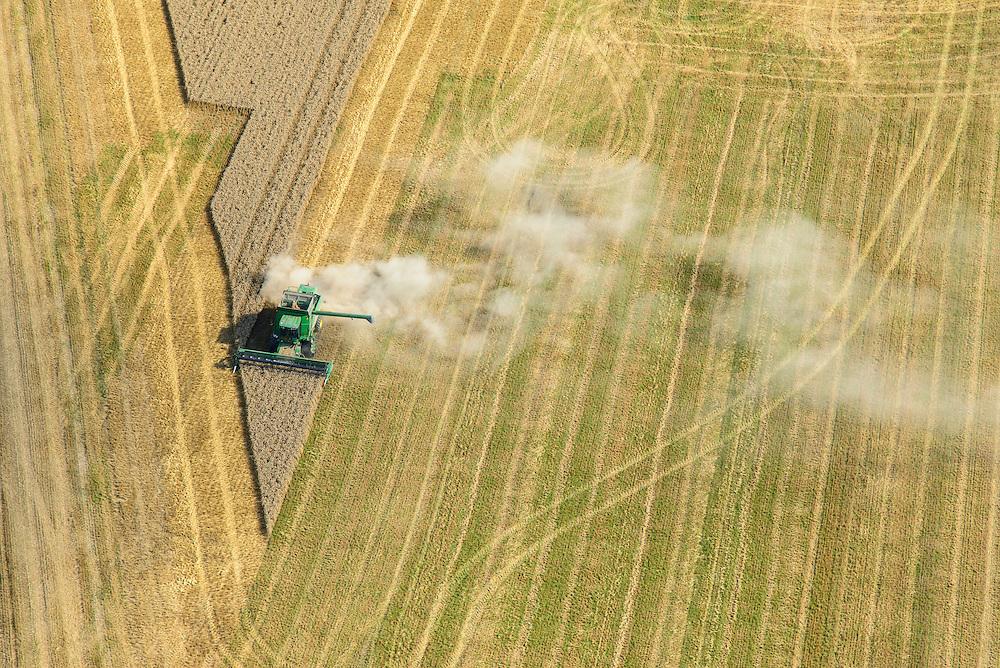 Nederland, Flevoland, Gemeente Dronten, 27-08-2013; maaien en dorsen van het graan met een John Deere combine veroorzaakt een stofwolk, ten noordoosten van Biddinghuizen.<br /> A John Deere combine causes a cloud of dust while mowing and grain threshing in the polder near Biddinghuizen.<br /> luchtfoto (toeslag op standaard tarieven);<br /> aerial photo (additional fee required);<br /> copyright foto/photo Siebe Swart.