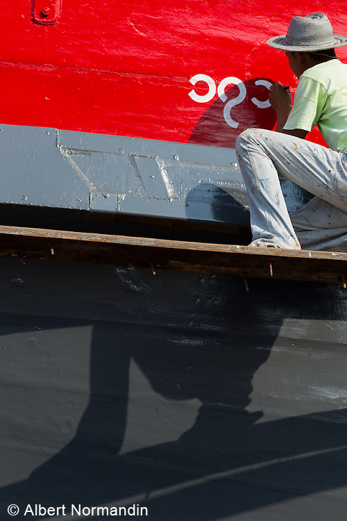 Worker painting name on red and grey ship, Tenasserim River shipyard.