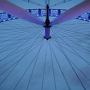 The spokes of the London Eye (formerly known as the Millenium Wheel) at dusk against an overcast sky.