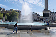 A young girl leaps in the air while running backwards and forwards through the spray from one of the fountains in Trafalgar Square, on 20th August 2020, in London, England. (Richard Baker / In Pictures via Getty Images)
