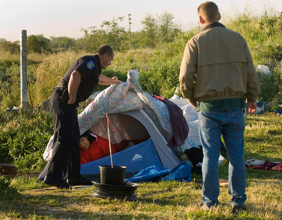 Sacramento police officer Mike Cooper lifts a blanket on the tent of a homeless woman Sophia as Garren Bratcher of Loaves & Fishes watches. They were reminding her that everyone had to leave Tent City. Bratcher is co-director of Friendship Park.