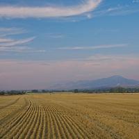 A cirrus cloud floats over the Bridger Mountains and harvested wheat fields near Bozeman, Montana.
