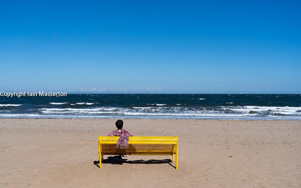 Portobello beach and promenade near Edinburgh during Coronavirus lockdown on 19 April 2020. Woman sits alone on yellow bench on the empty  beach.