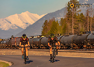 Couple road bicycling on Edgewood Road with Great Northern Mountain and railyard in backgorund in Whitefish, Montana, USA MR
