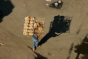 Seen from the minaret of a mosque in Cairo, a teenage boy delivers bread. Hungry Planet: What the World Eats (p. 121).