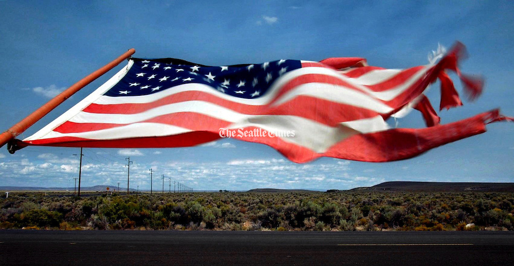 """Wind whips a flag along a fenceline south of Burns, Oregon in Harney County, one of the largest and least populated counties in America some have called """"The Big Empty.""""<br /> Alan Berner / The Seattle Times"""