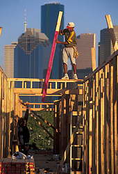 Stock photo of a construction worker standing on a structures wooden framing