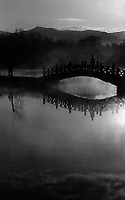 Silhouette bridge and reflection with early morning mist rising off the lake in grounds of the Imperial Summer resort in Chengde, China.