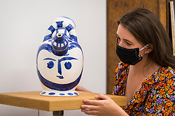 "© Licensed to London News Pictures. 01/09/2020. LONDON, UK. A staff member poses with ""Pichet à glace [Ice-pitcher] , 1952"" by Pablo Picasso.  Preview of ""Atelier Picasso"", a new exhibition recreating Pablo Picasso's studio in Cannes featuring his drawings, prints, ceramics and furniture.  The show is at Bastian gallery in Mayfair 3 September to 31 October 2020.  Visitors will be required to wear a facemask and practice social distancing.  Photo credit: Stephen Chung/LNP"