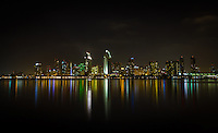 The downtown San Diego city skyline lights up the bay at night.  Viewed from Coronado.