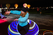 AARP's Carly Roszkowski spins a hula hoop as balloons inflate at the AARP Block Party at the Albuquerque International Balloon Fiesta in Albuquerque New Mexico USA on Oct. 8th, 2018.