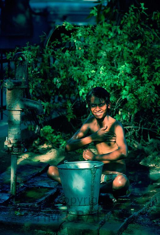 Boy washing at handpump, street scene, Delhi, India