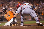 San Francisco Giants first baseman Brandon Belt (9) beats a tag by St. Louis Cardinals catcher Yadier Molina (4) at home at AT&T Park in San Francisco, Calif., on September 16, 2016. (Stan Olszewski/Special to S.F. Examiner)