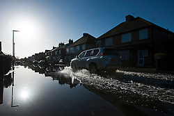 © London News Pictures. 16/02/2014. Egham, UK.  A four wheel drive car drives through flood water reflecting properties on a residential street in Egham, Surrey, that has been hit heavily by flooding. Photo credit : Ben Cawthra/LNP
