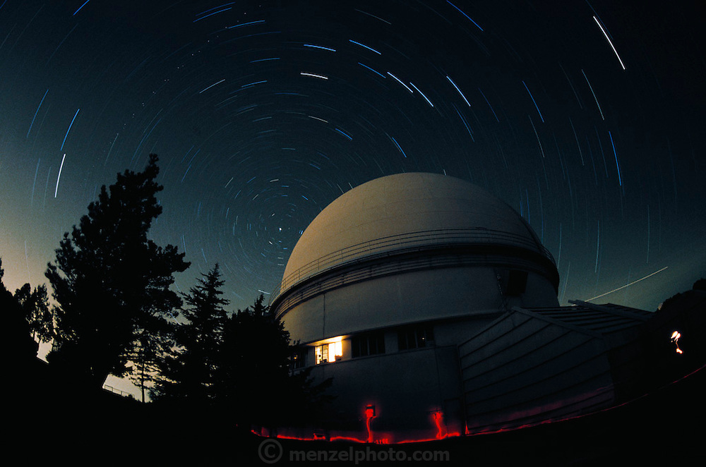 Lick Observatory. Time exposure image showing star trails over a telescope dome at the Lick Observatory on Mount Hamilton in California, USA. In the foreground are trails from red flashlights carried by astronomers so that their night vision is not affected. Completed in 1888 at an altitude of 1280 meters, Lick was the world's first permanent mountaintop observatory. Its location provided excellent viewing conditions for years until light pollution from the nearby city of San Jose began to interfere with results. In 1997 the observatory is operated by California University. Star trails are caused by what seems to be the motion of the stars due to the rotation of the Earth about its axis. (1996)