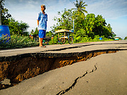 14 JULY 2015 - THAILAND:  A man looks at a damaged road in Pathum Thani province. The road bed collapsed because of subsidence. The drought that has crippled agriculture in central Thailand is now impacting residential areas near Bangkok. The Thai government is reporting that more than 250,000 homes in the provinces surrounding Bangkok have had their domestic water cut because the canals that supply water to local treatment plants were too low to feed the plants. Local government agencies and the Thai army are trucking water to impacted communities and homes. Roads in the area have started collapsing because of subsidence caused by the retreating waters. Central Thailand is contending with drought. By one estimate, about 80 percent of Thailand's agricultural land is in drought like conditions and farmers have been told to stop planting new acreage of rice, the area's principal cash crop.      PHOTO BY JACK KURTZ