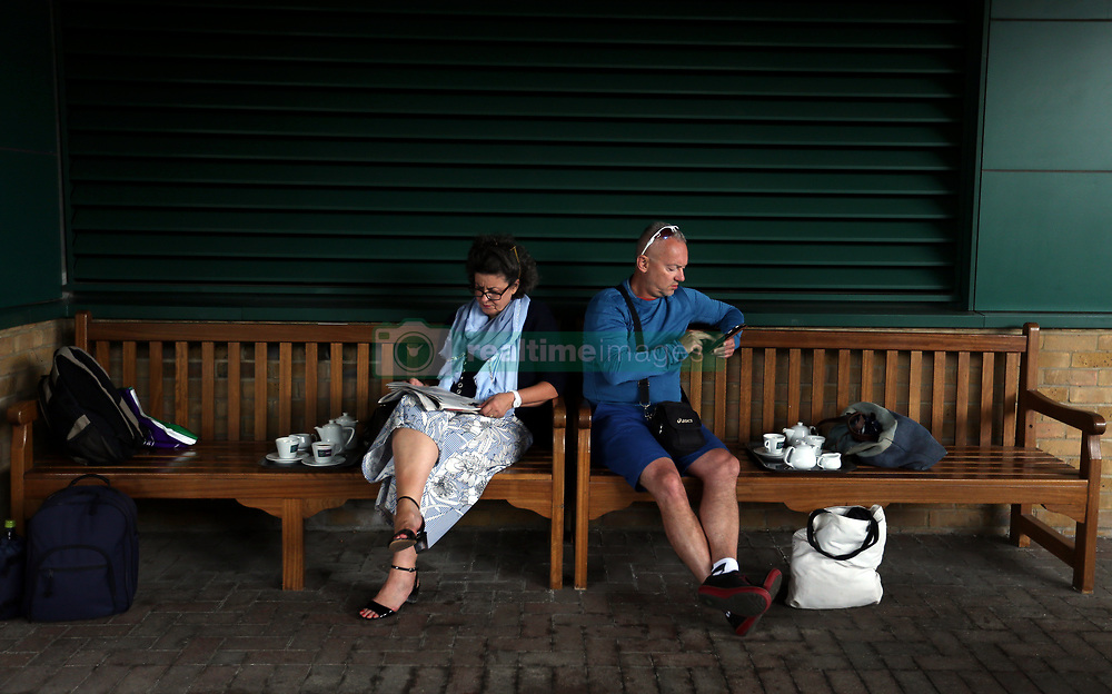 Spectators get out of the rain on day eight of the Wimbledon Championships at The All England Lawn Tennis and Croquet Club, Wimbledon.