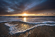 Waves pile foam crescents on the high tide mark at sunset in Winter at this West Anglesey beach near Rhosneigr