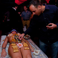Male guest eats sushi served on the body of naked woman following japanese traditions in a club in downtown Budapest, Hungary on September 23, 2011. ATTILA VOLGYI