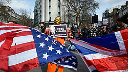 © Licensed to London News Pictures. 22/02/2020. LONDON, UK.  A person wearing a mask stands between the US and UK flags during a march from Australia House in Aldwych to Parliament Square in support of Wikileaks founder Julian Assange.  The full extradition trial of Mr Assange begins in London on 24 February.  Photo credit: Stephen Chung/LNP