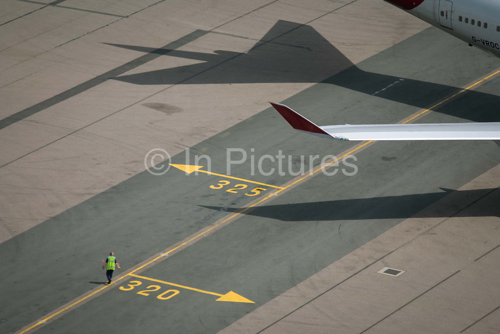 Aerial view (from control tower) of airport ramp marshal and airliner wing at London Heathrow airport. A ramp agent manages the start-up of a 747, standing on directional lines that help pilots navigate to specific locations around the airport of five terminals on a site that covers 12.14 square kilometres (4.69 sq mi). London Heathrow is a major international airport, the busiest airport in the United Kingdom and the busiest airport in Europe by passenger traffic. It is also the third busiest airport in the world by total passenger traffic, handling more international passengers than any other airport around the globe. From the chapter entitled 'Up in the Air' and from the book 'Risk Wise: Nine Everyday Adventures' by Polly Morland (Allianz, The School of Life, Profile Books, 2015).
