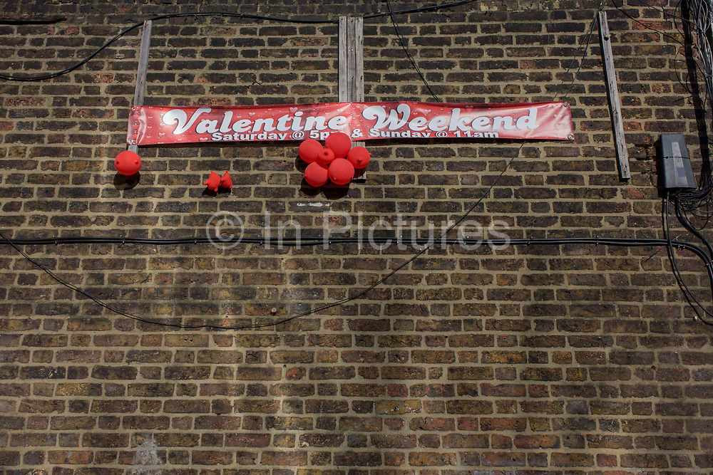 A clutch of deflated red love balloons and a Valentines Weekend banner on a brick wall in south London. Looking up we see a detail of the bright reds of the banner and balloons plus electrical and telephony wiring tacked along the bricks on Walworth in the London borough of Southwark. It is a scene of sadness and depression - a dystopian landscape of ended love after the annual celebration of amour and relationships. The depressed wall shows us the opposite of the perfect Valentine ideal.
