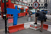 The back of a road crossing figure and resting pedestrian at the junction of Oxford Street and Tottenham Court Road. During the extensive construction of the capital's Crossrail transport project, street-level disruption has been massive and pedestrians and drivers have endured re-routing and hold-ups for many years. On the other side of these blue signs are human figures that stand at these junctions to stop crossing on red lights and thereby help stop accidents.