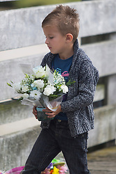 **CAPTION CORRECTION, CORRECT SPELLING OF BOYS NAME AND CLARIFICATION OF CAPTION**© Licensed to London News Pictures. 22/08/2016. Shoreham-by-Sea, UK. GEORGIO, the four year old son of Shoreham Crash victim Daniele Polito, lays flowers to remember his father at the one year anniversary of the Shoreham Airshow Plane crash. 11 victims died when a Hunter Hawker Jet crashed during the 2015 Shoreham Airshow. Photo credit: Hugo Michiels/LNP