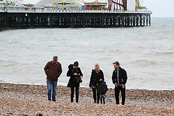 © Licensed to London News Pictures. 26/10/2014. Brighton, UK. A family taking a walk on Brighton beach. A cloudy day with possibility of some localised showers. The temperatures are expected to reach 15C in Brighton and the South Coast. Photo credit : Hugo Michiels/LNP