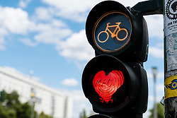 Detail of red stop light at  traffic lights for cyclists with red love heart in Berlin Germany