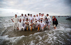 © London News Pictures. 17/09/2012. Southampton, UK.  The two teams line up before the match. Teams play a cricket match on the Bramble Bank in the middle of The Solent on September 17, 2012.  The annual cricket match between the Royal Southern Yacht Club and The Island Sailing Club, takes place on a sandbank which appears for 30 minutes at lowest tide. The game lasts until the tide returns. Photo credit : Ben Cawthra/LNP.