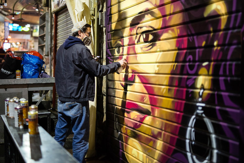 Artist Solomon Souza is seen as he spray-paints a portrait depicting Israeli-Arab news anchor Lucy Aharish over a closed shutter at the Mahane Yehuda Market, often called 'The Shuk' in Jerusalem, Israel, on February 24, 2016.