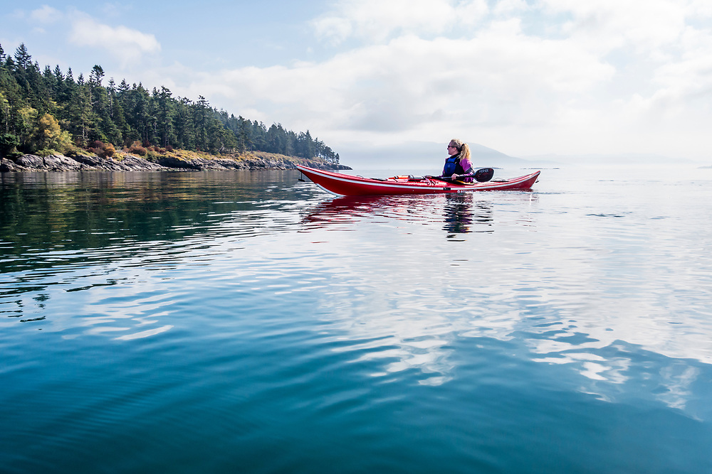 A woman sea kayaking in the morning off of Orcas Island in Rosario Strait, Washington, USA.